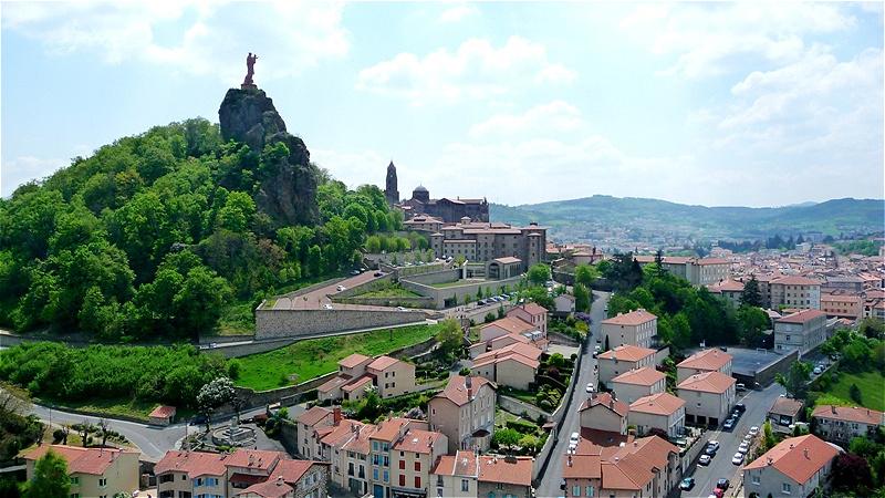 Blick von Saint Michel hinüber zur Kathedrale. Auf dem benachbarten Vulkankegel, dem Rocher Corneille, steht die Statue der Notre–Dame de la France