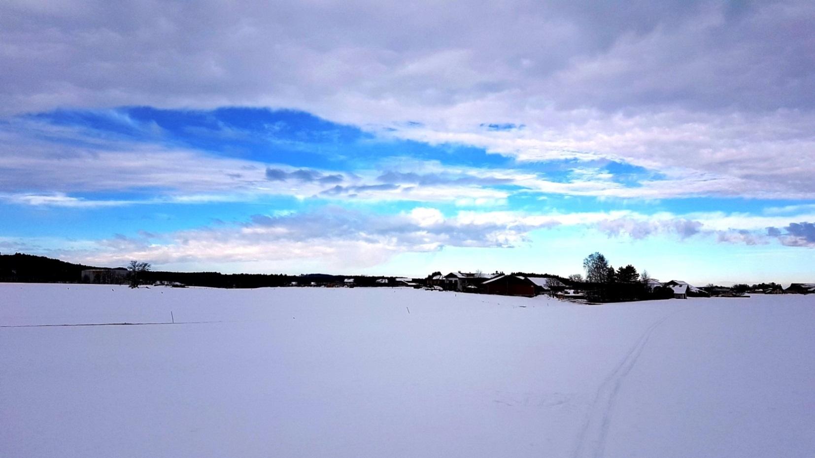 Blauer Himmel über der Ortschaft Holz