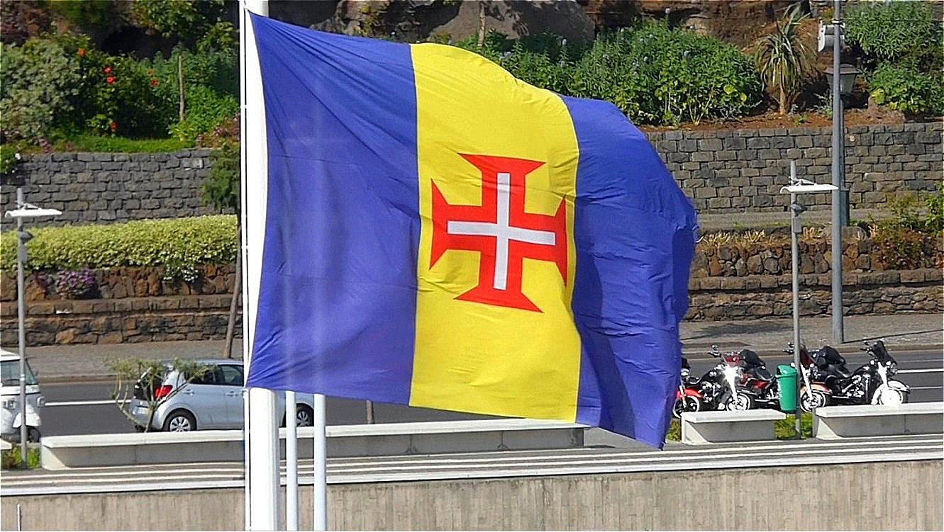 Madeiras Flagge - das rote Tatzenkreuz auf senkrechten blau-gelb-blauen Streifen. In der Mitte das Kreuz des Christusordens, der aus dem Templerorden hervorgegangen ist.