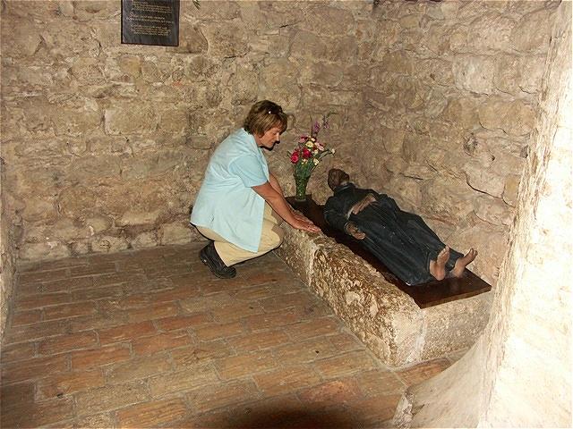 """Am Steinlager des Hl. Franz von Assisi im Inneren der """"Heiligen Hütte""""."""